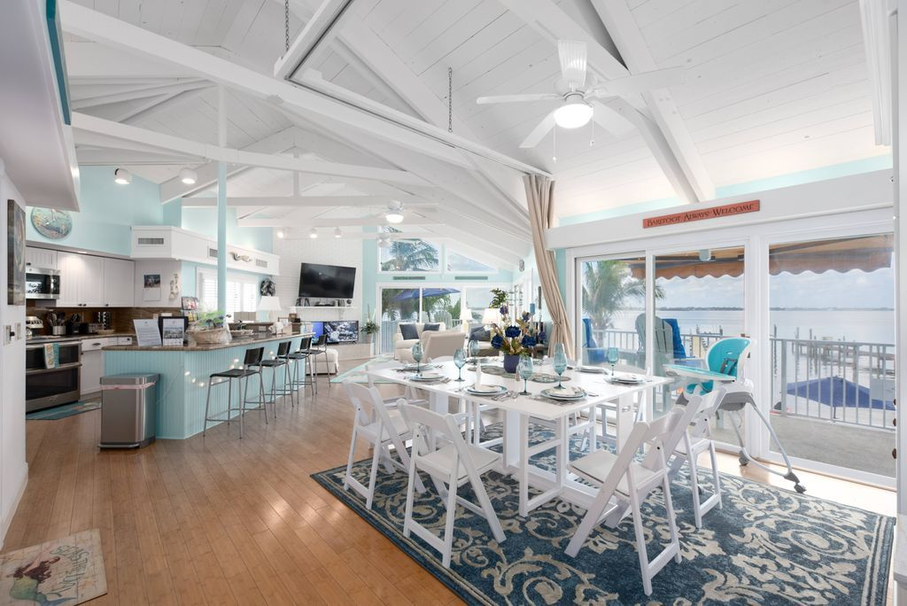 Open floor plan riverfront dining room with white table and chairs