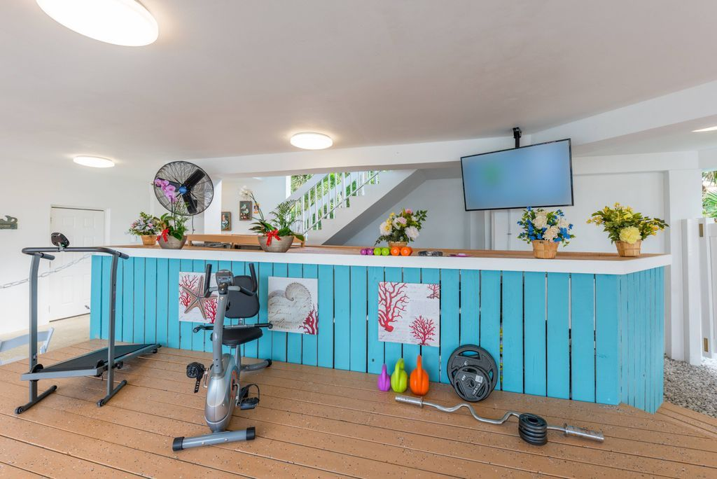 Fitness equipment including treadmill, free weights, and stationary bike on the covered deck of Aquarius riverfront beach home
