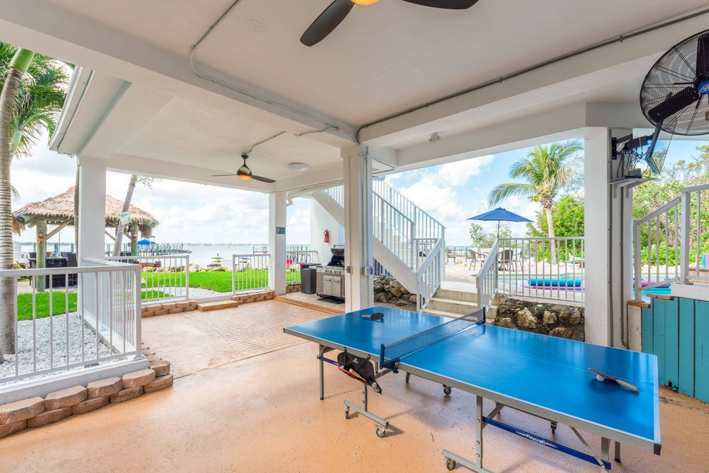 Outdoor covered ping pong table area with two ceiling fans