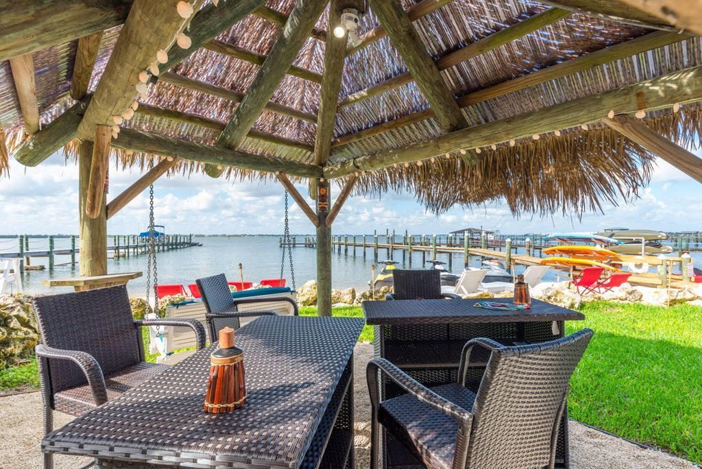 Tiki bar area with dark-colored patio furniture overlooking the Indian River