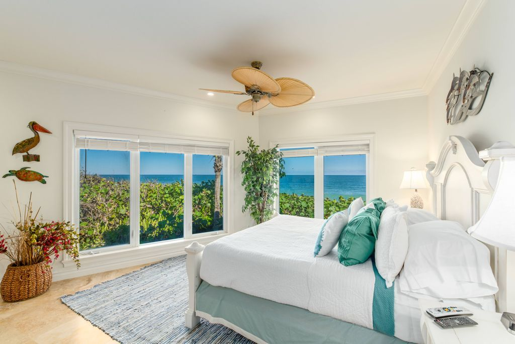 Oceanfront master bedroom suite with king bed and palm leaf ceiling fan